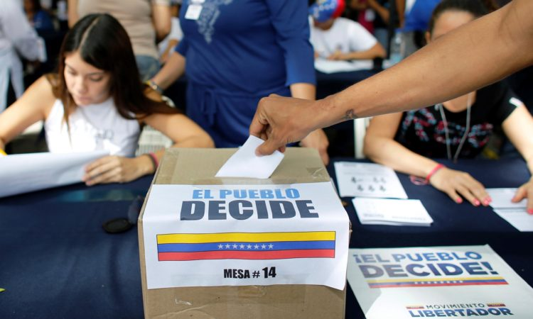 A man casts his ballot at a poll station during a symbolic referendum in Caracas, Venezuela, Sunday, July 16, 2017. Venezuela's opposition called for a massive turnout Sunday in a symbolic rejection of President Nicolas Maduro's plan to rewrite the constitution, a proposal that's escalating tensions in a nation stricken by widespread shortages and more than 100 days of anti-government protests. (AP Photo/Ariana Cubillos)