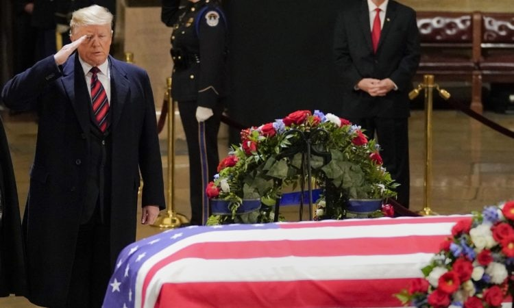President Donald Trump salutes alongside first lady Melania Trump in front of the flag-draped casket of former President George H.W. Bush in the Capitol Rotunda in Washington, Monday, Dec. 3, 2018. (AP Photo/Pablo Martinez Monsivais/Pool)