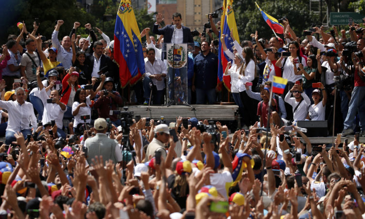 Anti-government protesters hold their hands up during the swearing-in of Juan Guaido, head of the National Assembly, as interim president of Venezuela during a rally demanding an end to the Nicolas Maduro regime and the restoration of democracy and the rule of law in Venezuela, January 23, 2019. (AP Photo/Fernando Llano)