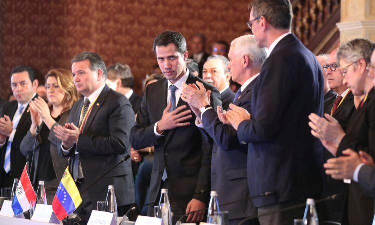 Flanked by Vice President Mike Pence, right center, Venezuela's interim president Juan Guaido, acknowledges the applause during a meeting of the Lima Group concerning Venezuela at the Foreign Ministry in Bogota, Colombia, Monday, Feb. 25, 2019. Pence arrived in the Colombian capital for an emergency summit of regional leaders to discuss Venezuela's crisis and immediately met with Guaido. In a speech to the group, Pence urged regional partners to freeze oil assets controlled by Maduro, transfer the proceeds to Guaido and restrict visas for Maduro's inner circle. (AP Photo/Martin Mejia)